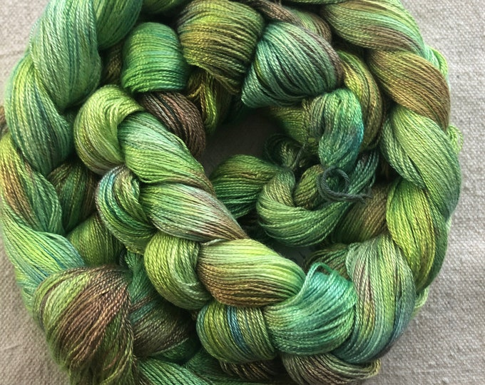 Hand-dyed, pre-wound, weaving warp chain, 8/2 lyocell Tencel, 200 and 300 ends, 4 7/8 yards long, in shades of bright greens and brown