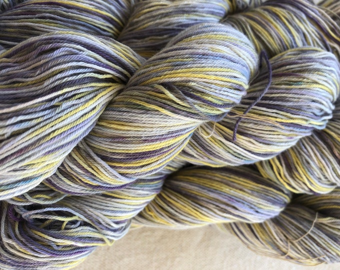 Hand-dyed, 10/3 cotton yarn, 500 yards skeins, in shades of yellow, purple, lavender, blue, and white