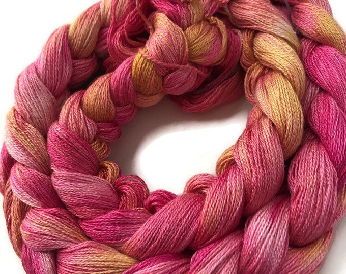 Hand-dyed, pre-wound weaving warp, 8/2 rayon, 200 ends, 6 3/8 yards long, in shades of pinks, peach, and golden yellow