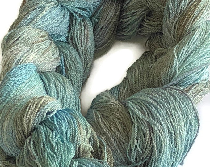 Hand-dyed, pre-wound weaving warp, 8/2 cotton and rayon, 300 ends, 3 1/4 yards long, in shades of green, blue, and brown
