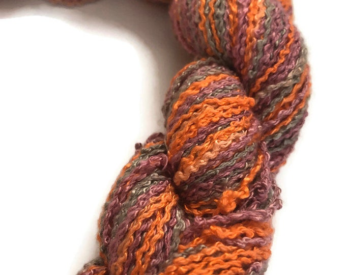Hand-dyed, cotton and rayon, boucle zigzag yarn, 200 yard skeins, in shades of orange, taupe grey, and salmon