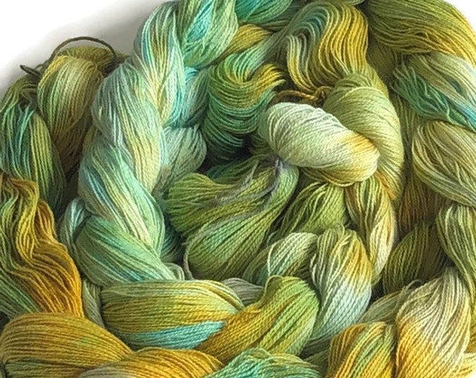 Hand-dyed, pre-wound weaving warp, 14/2 cotton, 300 ends, 4 7/8 yards long, in shades of greens, yellows, and golden yellow