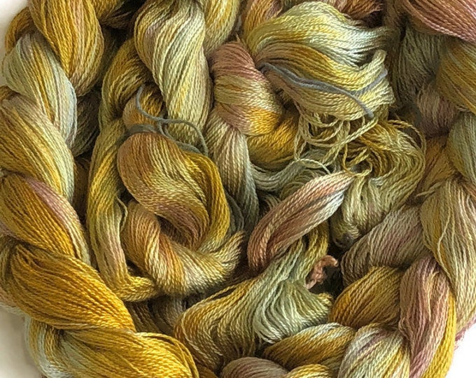 Hand-dyed, pre-wound weaving warp, 8/2 Tencel, 300 ends, 5 yards long, in shades of yellow, golden yellow, light green, and beige pink