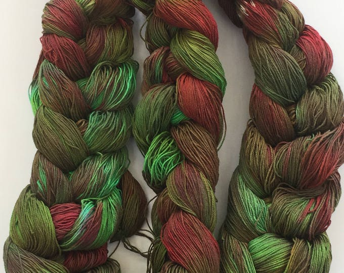 Hand-dyed, pre-wound weaving warp, 10/3 cotton, 300 ends, 7 3/4 yards long, in shades of greens, reds, and brown -108