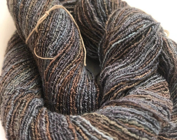 Hand-dyed, cotton and rayon, boucle yarn, 300 yard skeins, in shades of grey blue, taupe, and brown