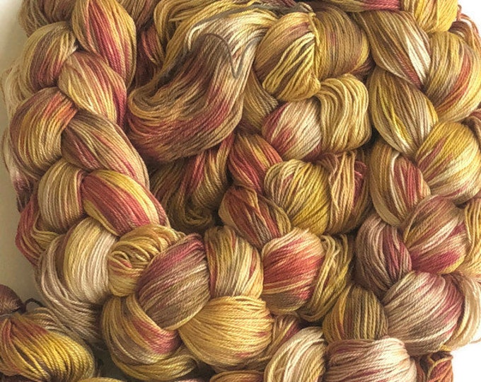 Hand-dyed, pre-wound weaving warp, 6.5/3 mercerized cotton, 300 ends, 6 3/8 yards long, in shades of yellow, rust, and brown