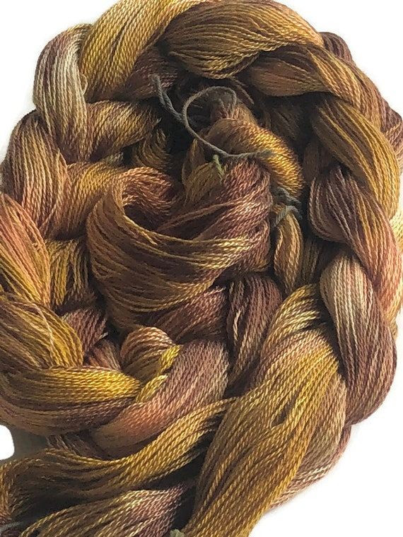 Hand-dyed, pre-wound weaving warp, 8/2 Tencel, 200 ends, 3 1/4 yards long, in shades of browns, golden yellow, and peach