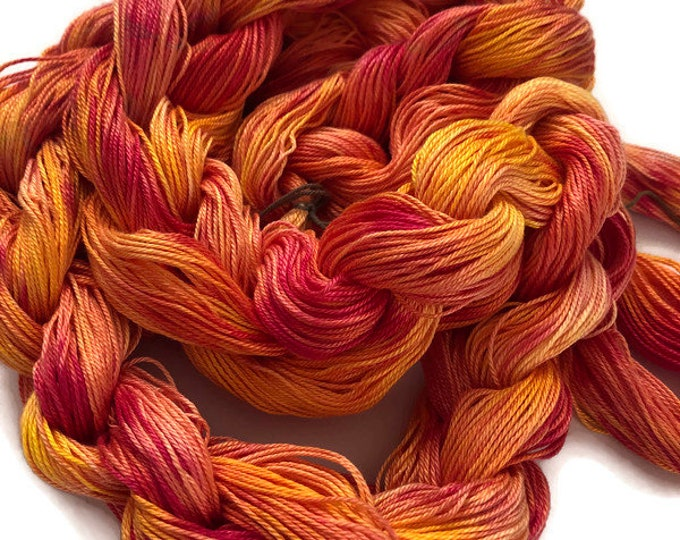 Hand-dyed, pre-wound weaving warp, 6.5/3 mercerized cotton, 100 ends, 6 1/2 yards, in shades of pink, orange, and yellow