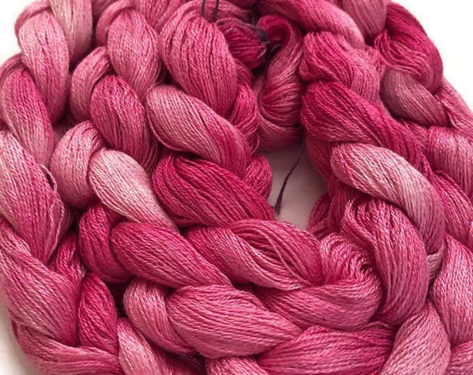 Hand-dyed, pre-wound weaving warp, 8/2 rayon, 200 ends, 7 3/4 yards long, in shades of pinks from pale to dark