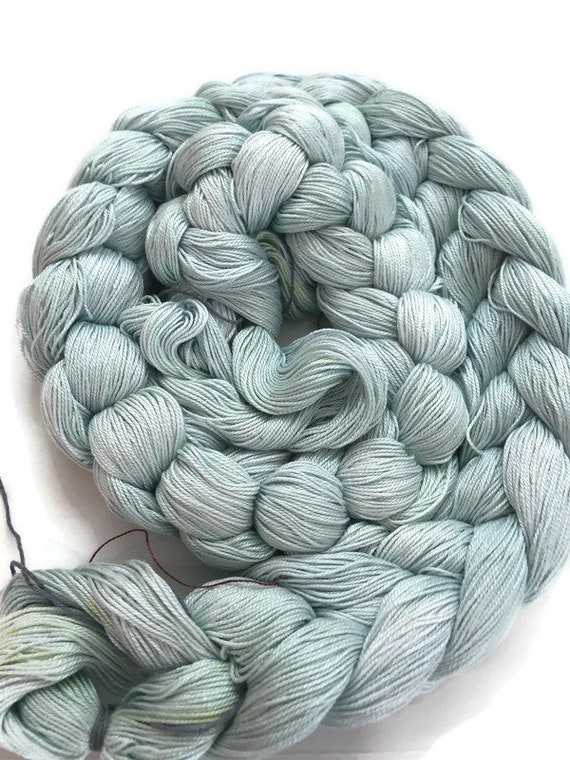 Hand-dyed, pre-wound weaving warp, 6.5/3 mercerized cotton, 200 ends, 6 1/2 yards long, in shades of pale to light blues