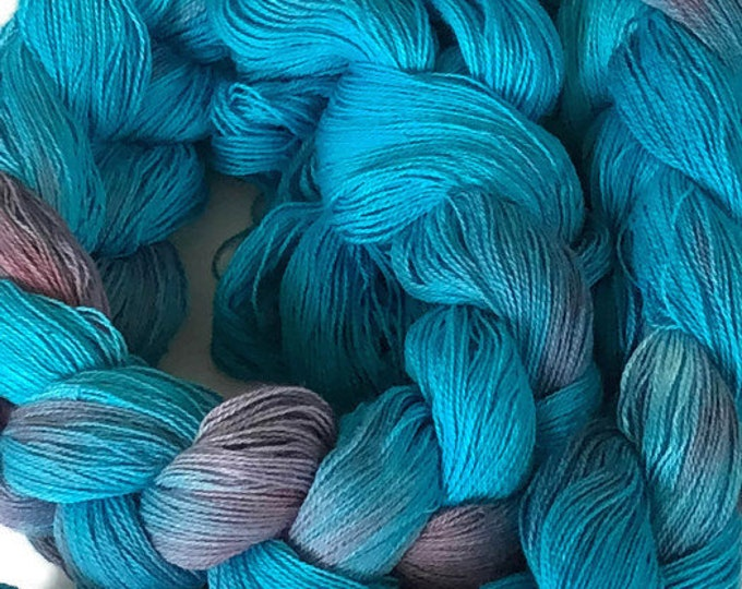 Hand-dyed, pre-wound weaving warp, 14/2 cotton, 400 ends, 4 3/4 yards long, in shades of turquoise, blue, and rose pink