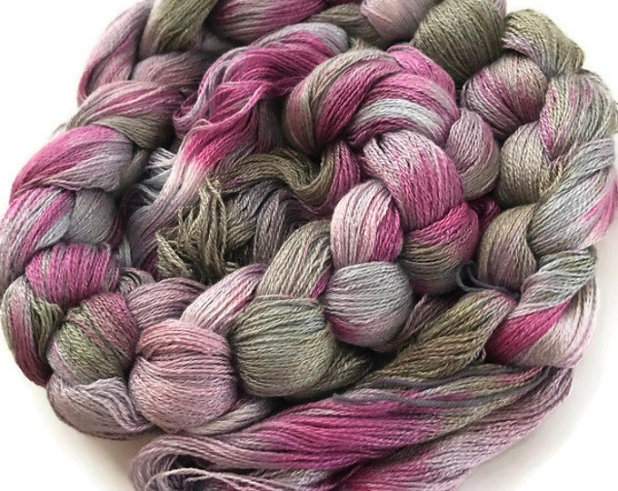 Hand-dyed, pre-wound weaving warp, 8/2 rayon, 300 ends, 4 3/4 yards long, in shades of grey, lavender, and pink