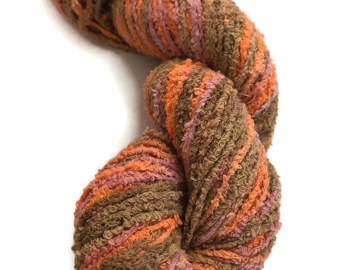 Hand-dyed cotton boucle yarn, 100 yard skein, in shades of orange, peach, pink, beige, and brown