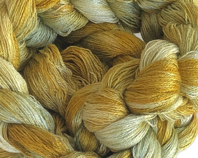 Hand-dyed, pre-wound weaving warp, 8/2 rayon, 300 ends, 7 3/4 yards long, in shades of yellow, golden yellow, and light green