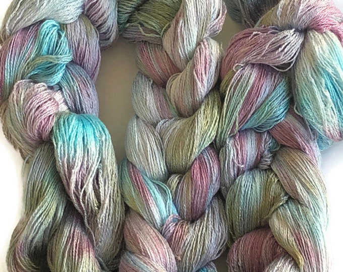 Hand-dyed, pre-wound weaving warp, 8/2 rayon, 400 ends, 4 3/4 yards long, in shades of blue, pink, lavender, and greyed green