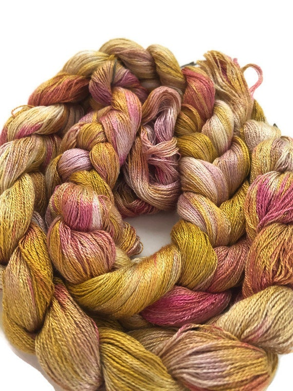 Hand-dyed, pre-wound weaving warp, 8/2 rayon, 300 ends, 6 1/4 yards long, in shades of golden yellow, beige, and pinks