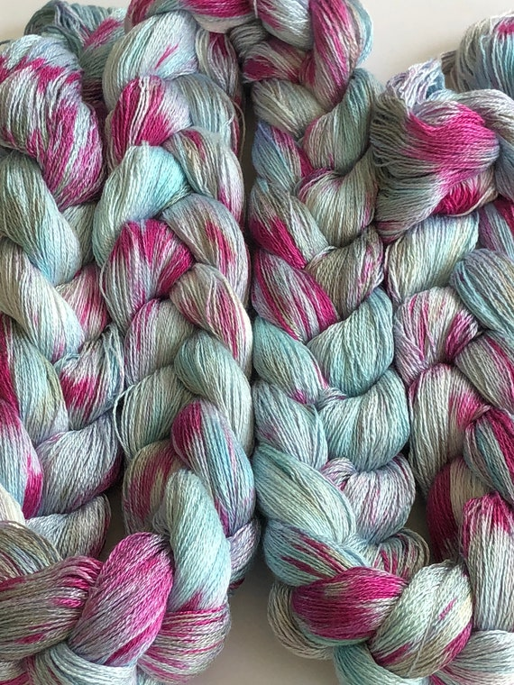 Hand-dyed, pre-wound weaving warp, 8/2 rayon, 400 ends, 7 3/4 yards long, in shades of light blue, dark pink, silver and greyed green