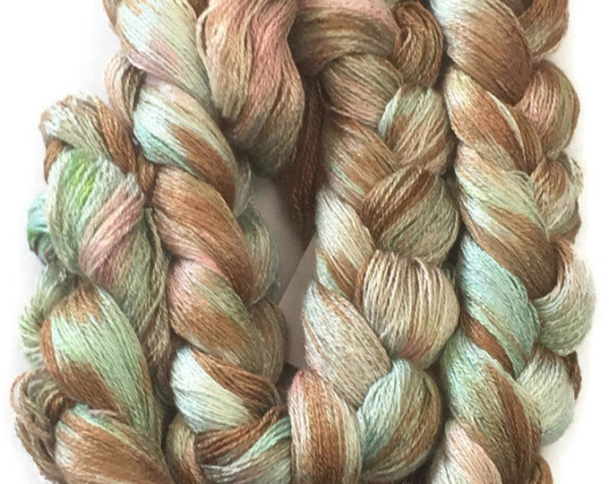 Hand-dyed, pre-wound 8/2 rayon weaving warp, 300 ends, 6 yards, in shades of green, brown, and pink -40