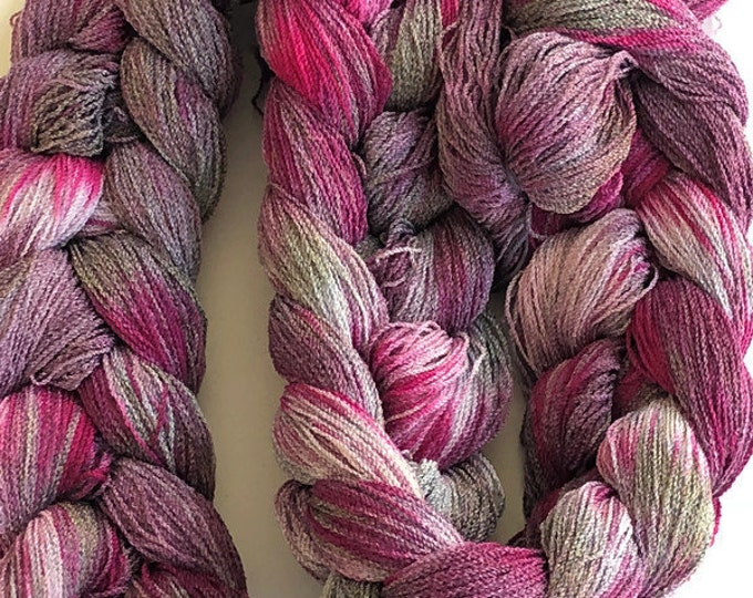 Hand-dyed, pre-wound weaving warp, 8/2 cotton and rayon, 300 ends, 6 1/4 yards long, in shades of greys, pinks, and red purples