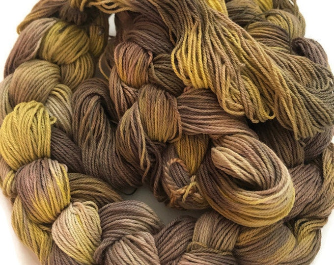 Hand-dyed, pre-wound weaving warp, 10/3 cotton, 3 3/4 yards long, in shades of brown, beige, yellow, and natural