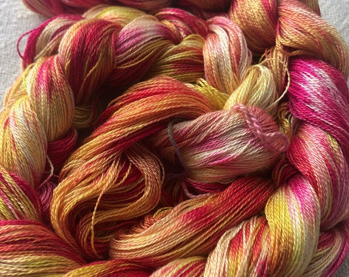 Hand-dyed, pre-wound weaving warp chain, 8/2 Tencel, 3 7/8 yards long, 100, 200. and 300 ends, in shades of red, pink, and yellow