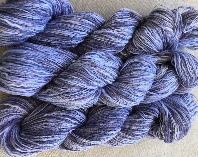 Hand-dyed, cotton thick and thin yarn, 500 yard skeins, in shades of purple and lavender with a small amount white