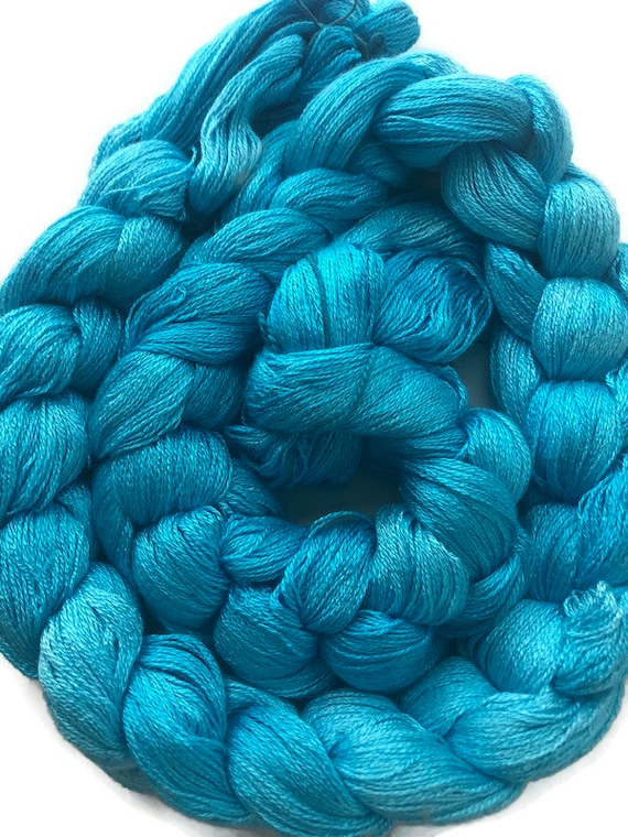 Hand-dyed, pre-wound weaving warp, 8/2 rayon, 300 ends, 6 1/4 yards long, in shades of turquoise