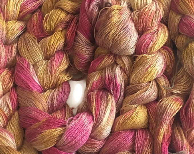 Hand-dyed, pre-wound weaving warp, 8/2 rayon, 200 ends, 7 3/4 yards long, in shades of pinks and golden yellows