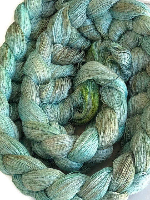 Hand-dyed, pre-wound weaving warp, 8/2 rayon, 400 ends, 7 3/4 yards long, in shades of light aqua blue, green, and grey
