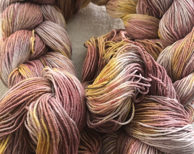 Hand-dyed, pre-wound, weaving warp chain, 10/3 cotton, 200 ends, 3 3/4 yards long, in shades of pinks, yellow, and natural