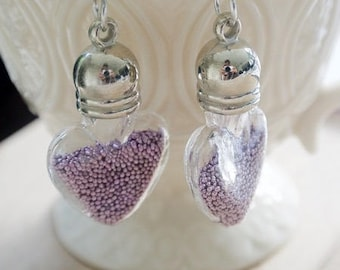 Glass heart earrings filled with purple microbeads