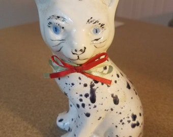 White black spotted cat figurine with red neck tie