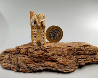 Single miniature cottage on driftwood