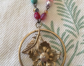 Adorable long pendant necklace made with upcycled vintage jewelry and beads. Gorgeous and unique vintage flower pendant is the centerpiece
