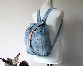 Handmade unique gray denim backpack with purple accents and embellishments