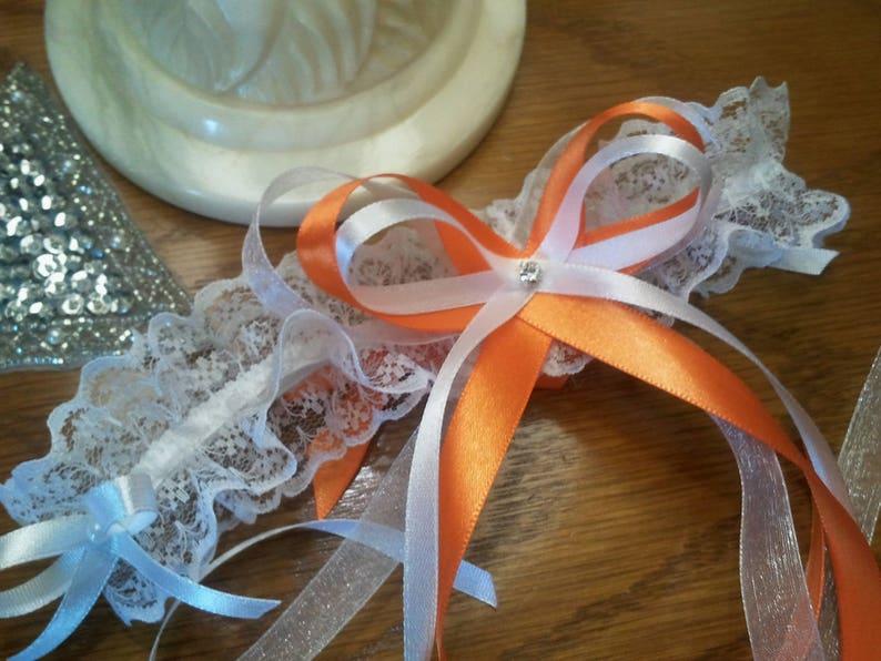 Orange wedding garter white lace trimmed with satin ribbon bows