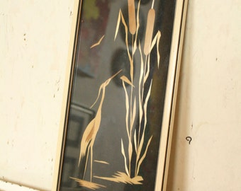 Framed vintage marquetry heron in the rushes.