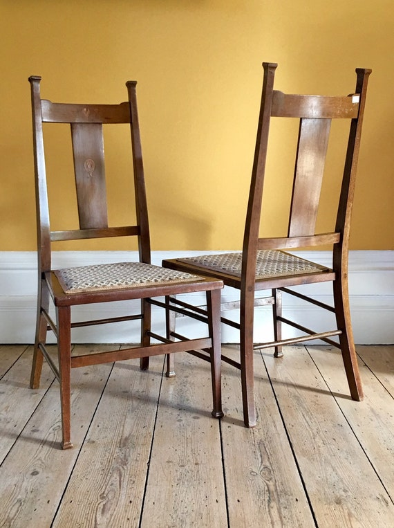 Pair of Arts and crafts dining chairs with inlaid marquetry motifs and embroidered seats