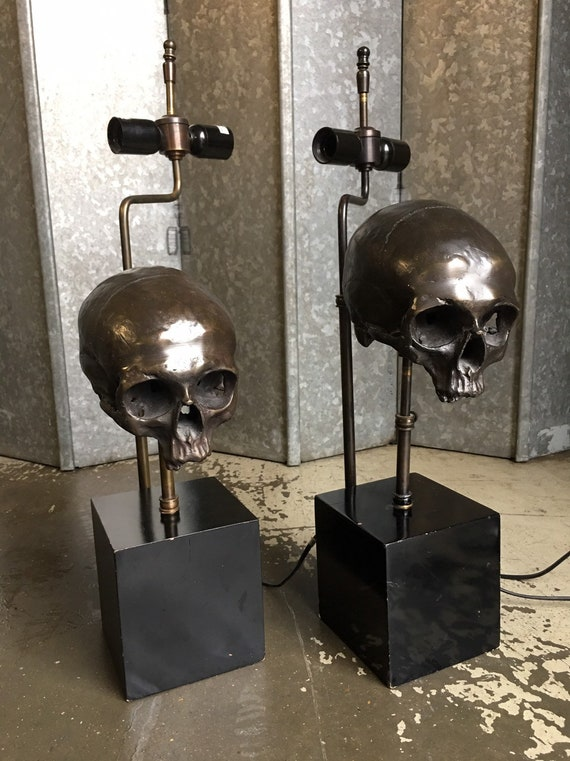 A pair of Eichholtz Extruder bronzed skull lamps with black base