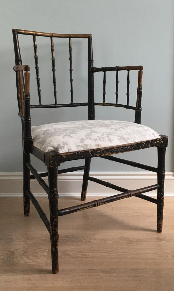An early 19th century Sussex Morris style ebonised faux bamboo chinoiserie carved ash armchair with upholstered seat.
