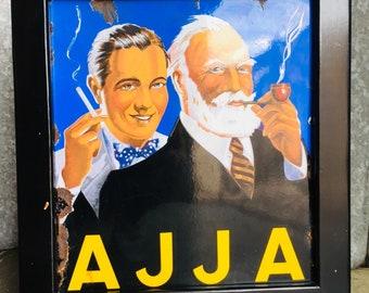 Antique enamel advert for Ajja tobacco in black wooden frame