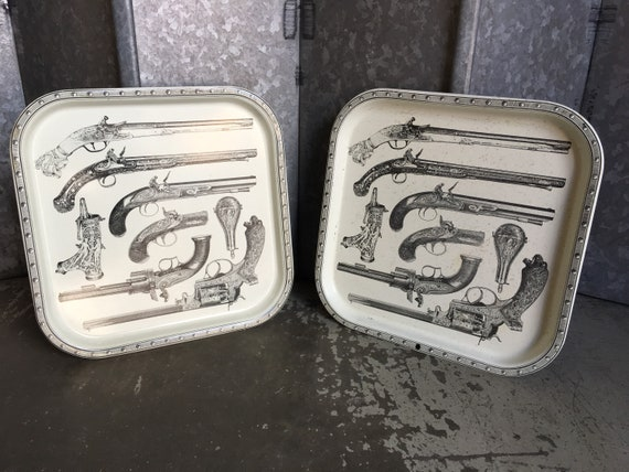 Vintage mid century pair of Piero Fornasetti trays featuring pistols and gunpowder pouches