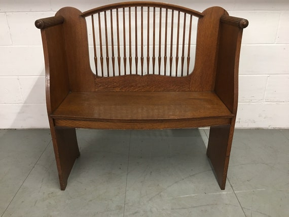 "An Arts and Crafts oak settle, with shaped spindled open back, bowfronted seat and scroll shaped ends, 38"" x 16"" x 38"""
