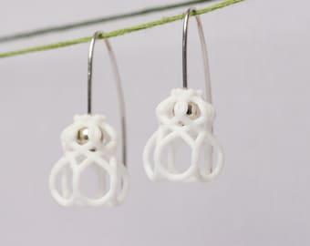 white dangle earrings in an elegant flower design made of sterling silver and nylon