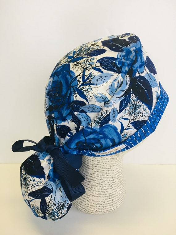 6d75bbde19f Ponytail Scrub Cap with a white fabric and flowers in shades
