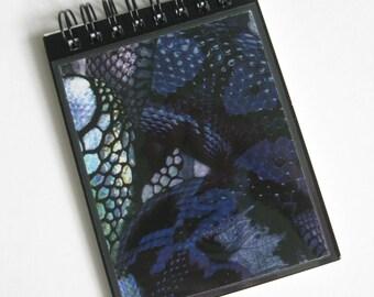 "Alexander McQueen A7 (11x8cm) spiral-bound notebook made with ""Black Snake' print paper."