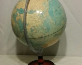 Vintage world globe sitting on wood stand.