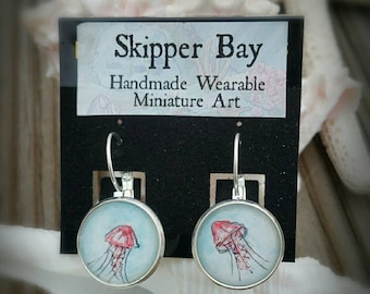 Jellyfish earrings hand-painted in watercolor. Pink jellyfish and teal or blue water, silver-plated earrings.
