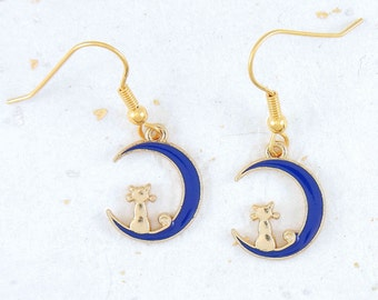 Tiny gold cats sitting on a blue enamelled moon crescent on hypoallergenic golden stainless steel hooks