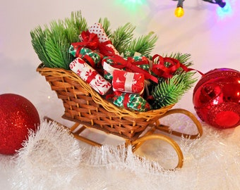 wicker christmas sleigh filled with fabric wrapped presents and evergreen boughs vintage woven sleigh basket